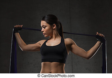 woman with expander exercising in gym - fitness, sport,...