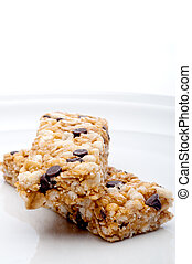 vertical close up of two granola bars on a white plate
