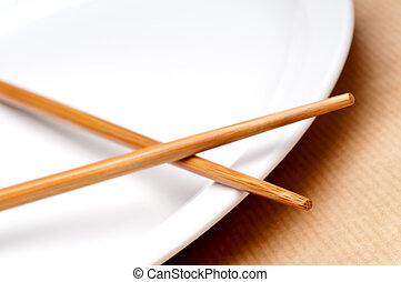 a tilted horizontal macro of a pair of chopsticks on a white plate