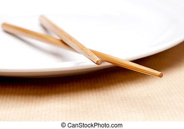 a horizontal macro of a pair of chopsticks on a white plate