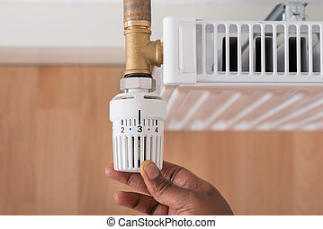 Persons Hand Holding Radiator Thermostat - Close-up Of...