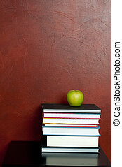 Vertical image of a stack of books with a green apple