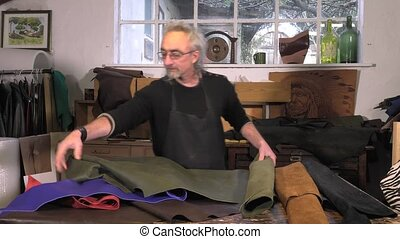 leather goods craftsman at work - choice of leather in...