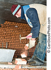 worker bricklayer during a brickwork - construction mason...
