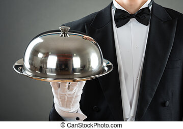 Midsection Of Waiter Holding Tray With Cloche