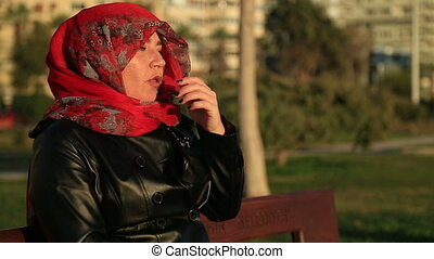 Sick muslim woman sneezing - Arabic muslim woman wearing red...