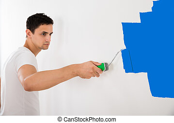 Man Painting Wall With Blue Paint Roller - Young man...