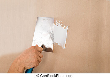 Hand Using Putty Knife On Brown Wall - Cropped hand of man...