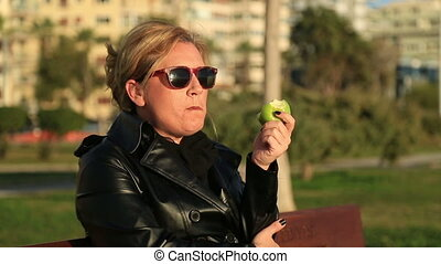 Woman eating apple - Portrait of a woman sitting on a park...