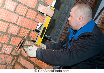worker checking a brickwork with level - construction mason...