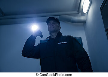 Security Guard Searching With Flashlight In Office - Mature...