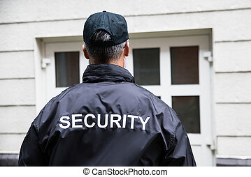 Security Guard Standing Outside Building - Rear view of...