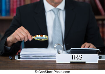 Auditor Examining Documents With Magnifying Glass At Table -...