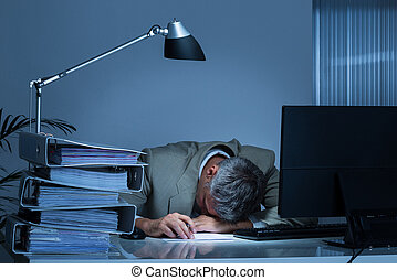 Businessman Leaning Head On Desk By Binders While Working...
