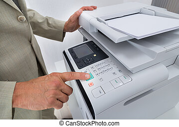 Midsection Of Businessman Pressing Printers Button -...