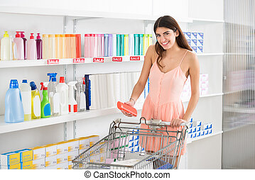 Woman Buying Beauty Product In Supermarket - Smiling young...