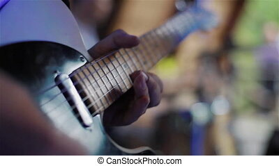 Guitarists hands playing electric guitar