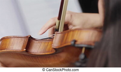 Female hand plucking violin strings - Playing violin with...