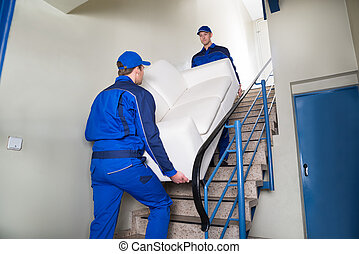 Movers Carrying Sofa On Steps - Male movers carrying sofa...