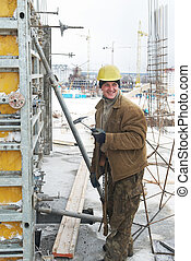 worker with hammer assembling formwork - construction worker...