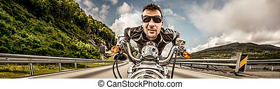 Funny Biker in sunglasses and leather jacket racing on...