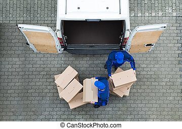 Delivery Men Unloading Cardboard Boxes From Truck On Street...