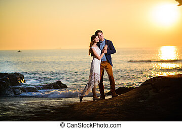 Couple in love watching a sunset on the beach