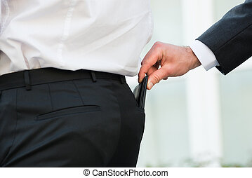 Hand Pickpocketing Wallet Of Businessman - Cropped hand...