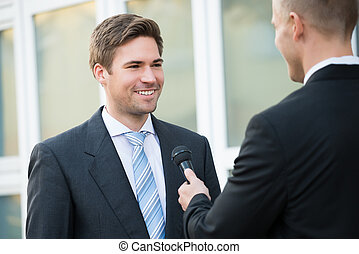 Journalist Taking Interview Of Happy Businessman