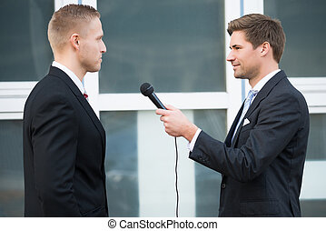 Journalist Interviewing Businessman Outdoors - Side view of...