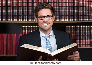 Advocate Reading Book At Courtroom - Young male advocate...