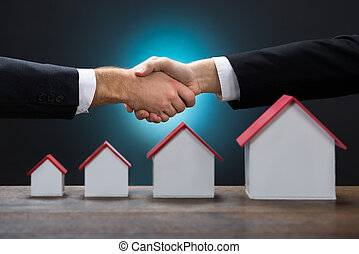 Businessmen Shaking Hands By Various Size Of House Models -...
