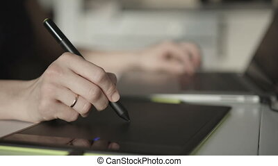 woman designer draws on a graphics tablet - woman the...