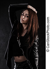 Beautiful young woman with a chain over black background