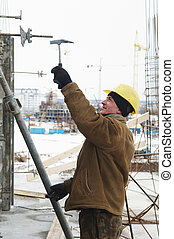 worker with hammer assembling formwork