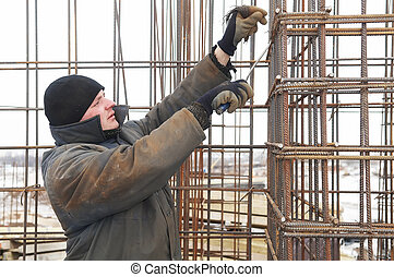 worker making a metal lattice at construction site - worker...