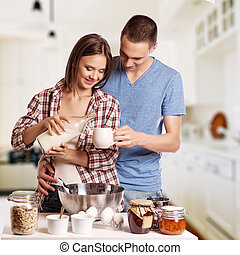 happy young couple have fun in modern wooden kitchen indoor...