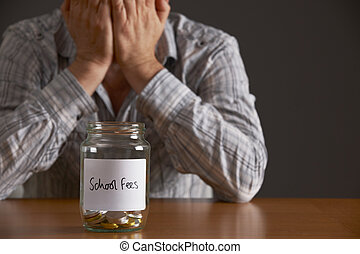 Man With Head In Hands Looking At Jar Labelled School Fees