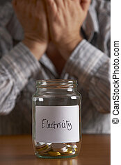 Man With Head In Hands Looking At Jar Labelled Electricity