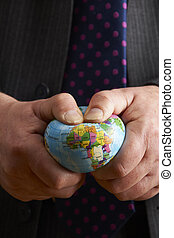 Businessman Squeezing Globe Over Africa