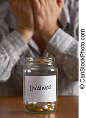 Man With Head In Hands Looking At Jar Labelled Christmas