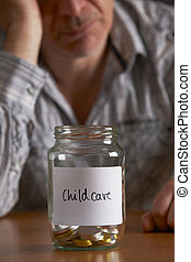 Depressed Man Looking At Empty Jar Labelled Childcare