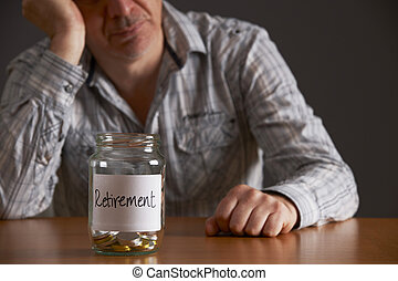 Depressed Man Looking At Empty Jar Labelled Retirement