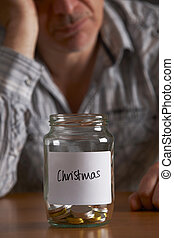 Depressed Man Looking At Empty Jar Labelled Christmas
