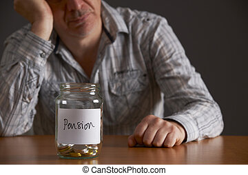 Depressed Man Looking At Empty Jar Labelled Pension