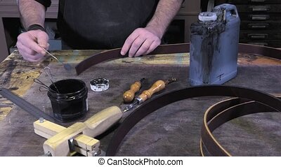 leather goods craftsman at work - slices dyeing leather...
