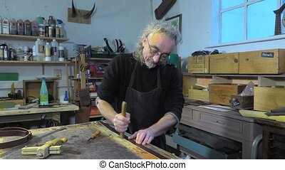 leather goods craftsman at work - Marking the edges of the...