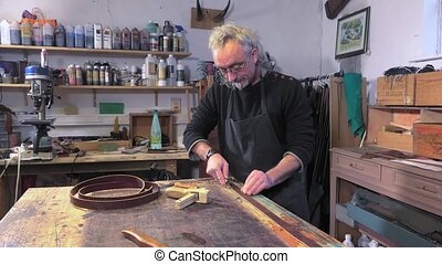 leather goods craftsman at work - leather cutting area for...