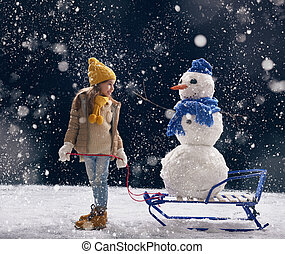 girl plaing with a snowman - happy child girl plaing with a...