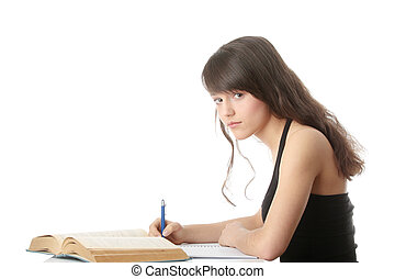Teen girl learning at the desk, isolated on white